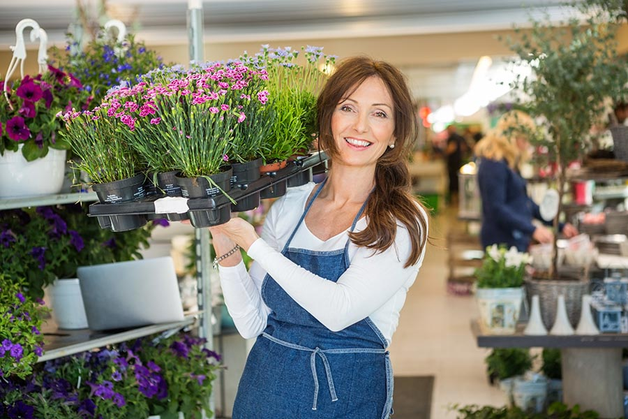 Business Insurance - Flower Shop Owner in a Denim Apron Smiles and Carries a Large Tray of Potted Flowers, With House Plants, Hanging Baskets and Customers Behind Her
