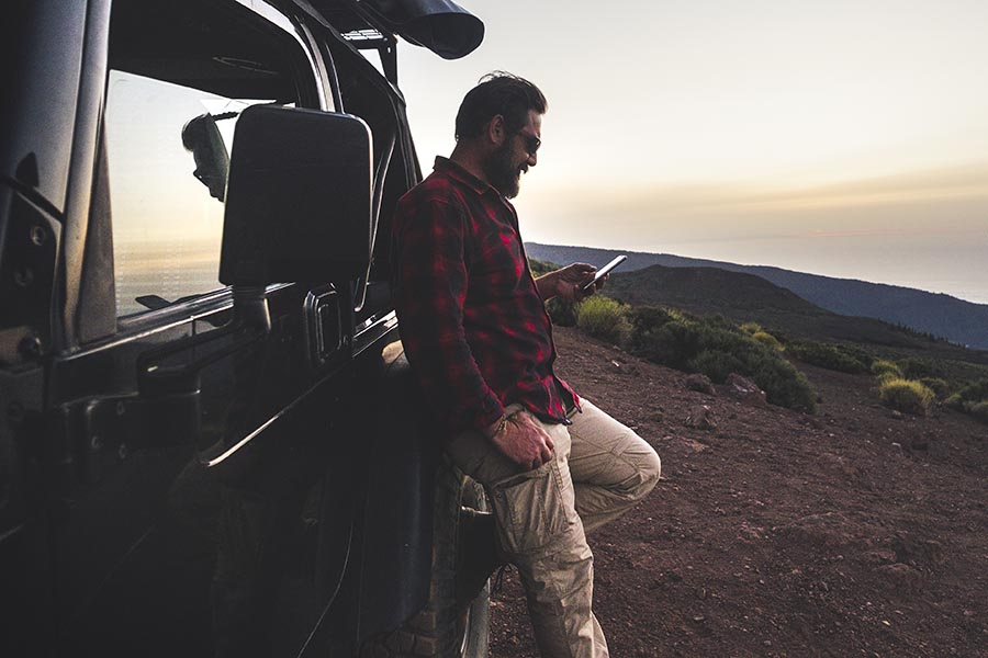 Contact Us - Young Man Parks His Car on a Hill Overlooking Mountains, Leaning Against His SUV and Making a Call on His Phone