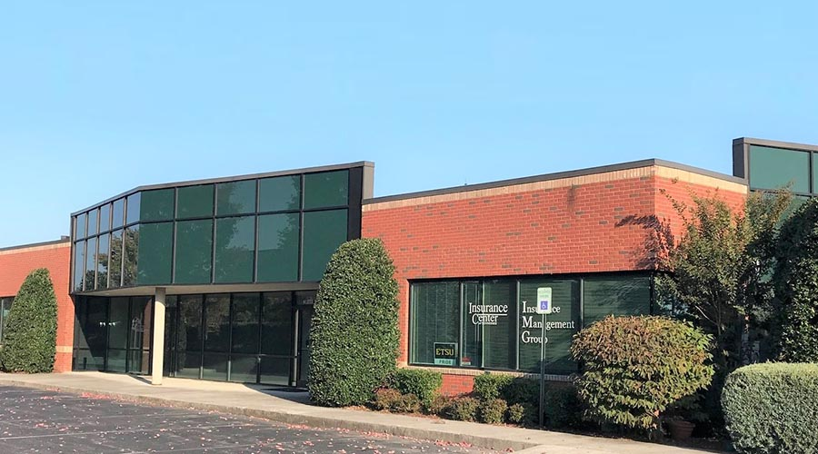 About Our Agency - Brick and Green Glass Office Building With Manicured Landscaping, With Sidewalk, Bright Blue Sky Overhead